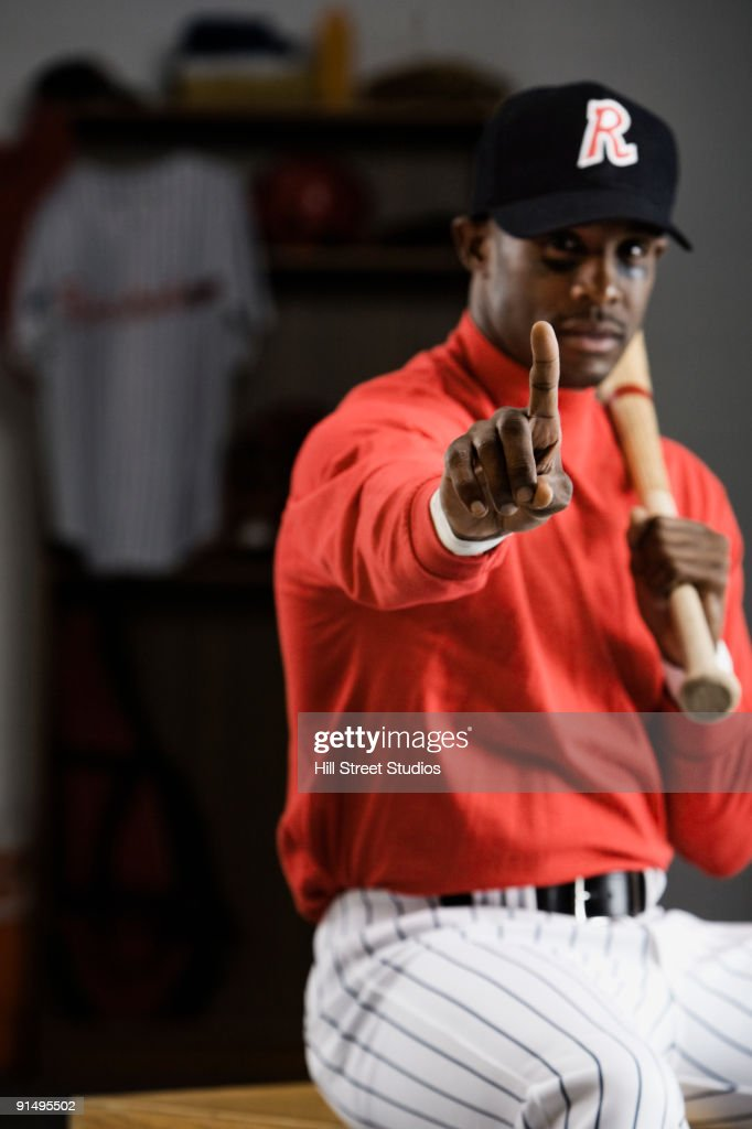 African Baseball Player Making Number One Gesture In Locker Room Stock Photo