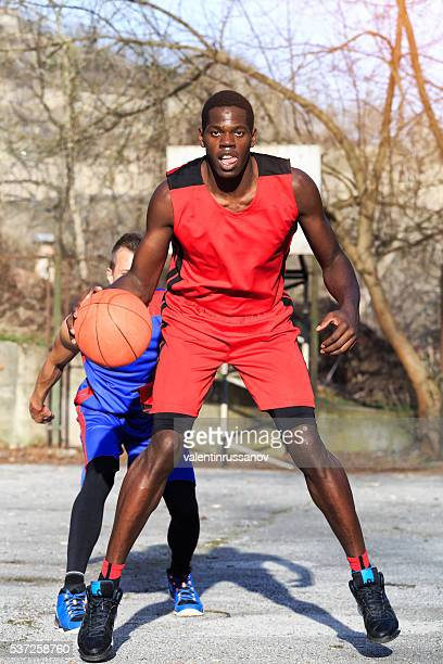 African basketbal player dribbling on street court