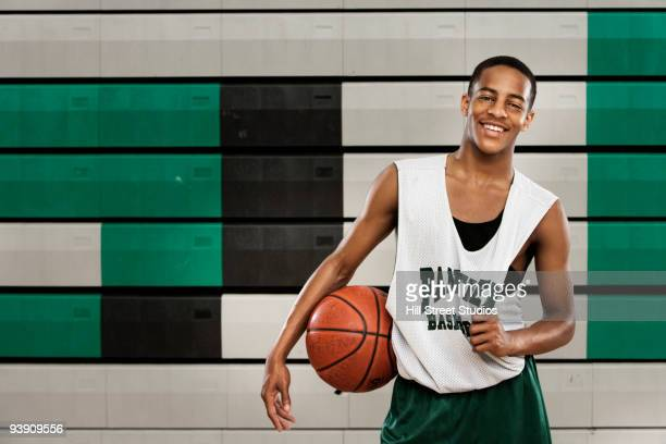 African basketball player holding ball and smiling in gym