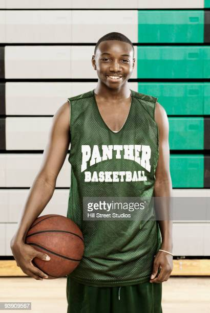 African basketball player holding ball in gym