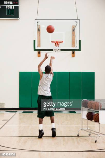 African basketball player practicing free throws in gym