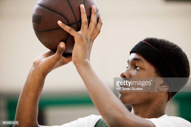 african basketball player shooting basketball in gym - ショットを決める ストックフォトと画像