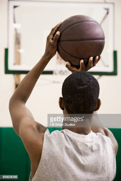 African basketball player shooting free throw in gym