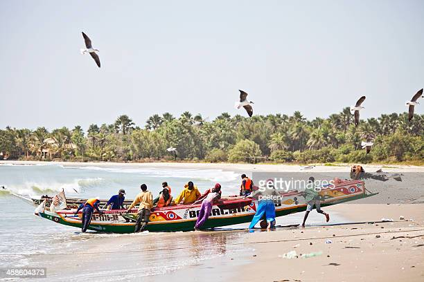 African beach scene with fishing boat.