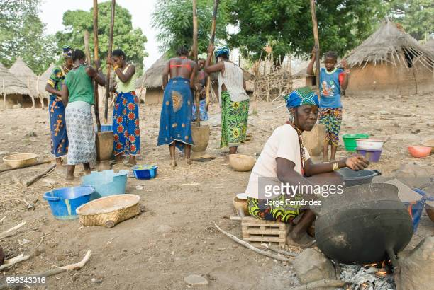 African bedik women preparing food outside with giant iron pots