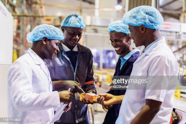 african bottling plant workers having a discussion about new product - may day international workers day stock pictures, royalty-free photos & images