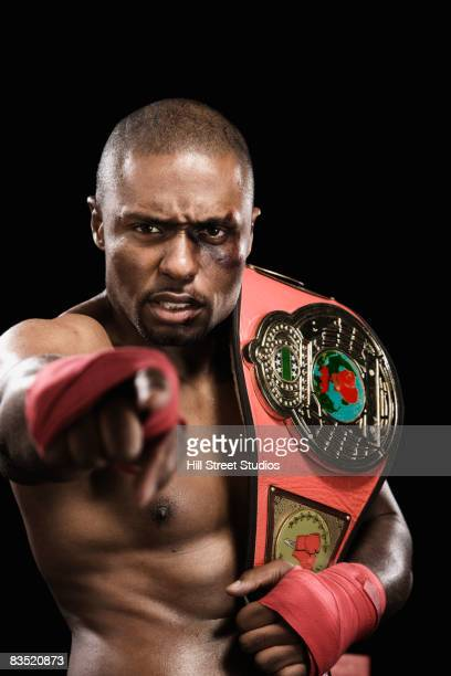 African boxer holding championship belt