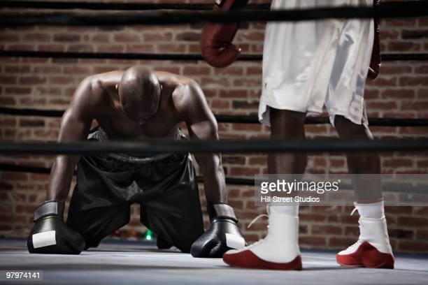African boxer kneeling on boxing ring mat