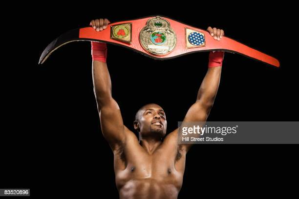African boxer lifting championship belt