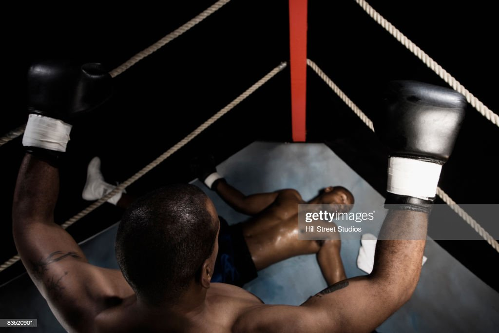 African boxer standing over knocked out opponent : Stock Photo