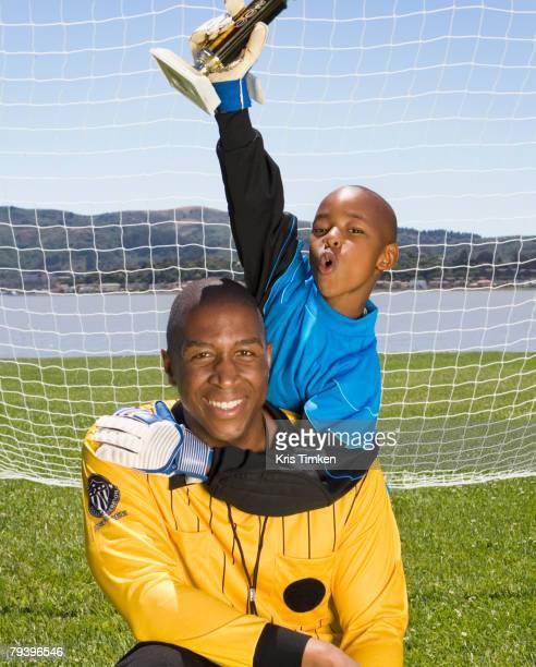 african boy and coach with soccer trophy - uniforme de equipe - fotografias e filmes do acervo