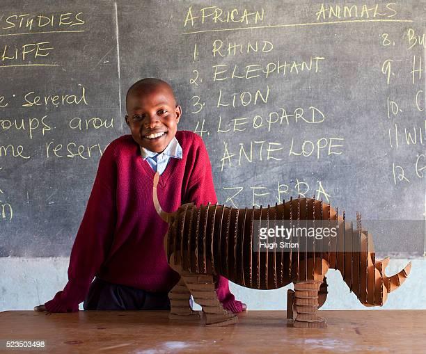 african boy and rhinoceros model at classroom - hugh sitton bildbanksfoton och bilder