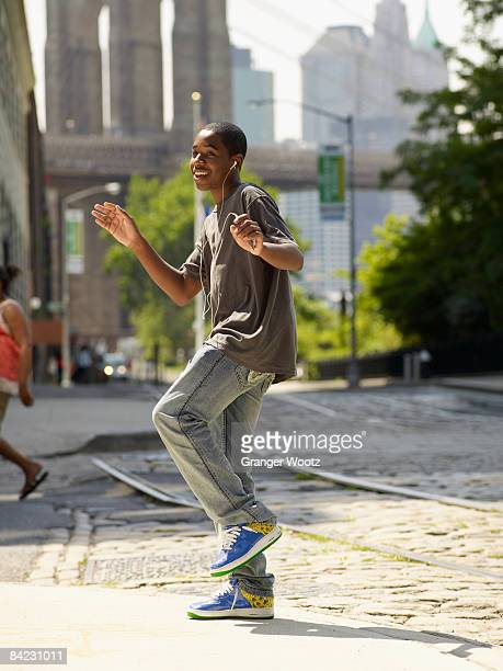 African boy dancing to music in urban setting