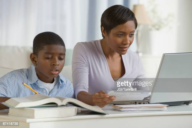 African boy doing homework next mother on computer