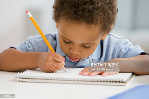 african boy drawing on notebook - 綴り ストックフォトと画像