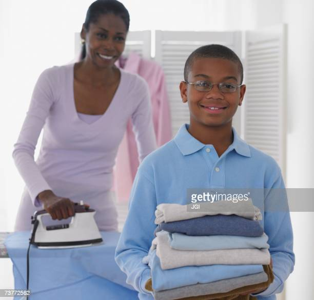 African boy helping mother with laundry