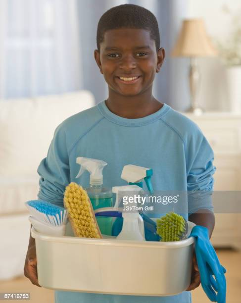 African boy holding bucket of cleaning supplies