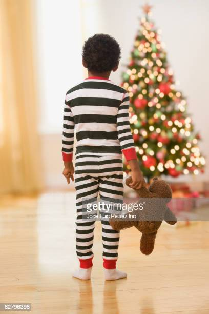 African boy in pajamas with teddy bear looking at Christmas tree