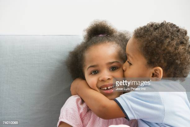 African boy kissing sister's cheek