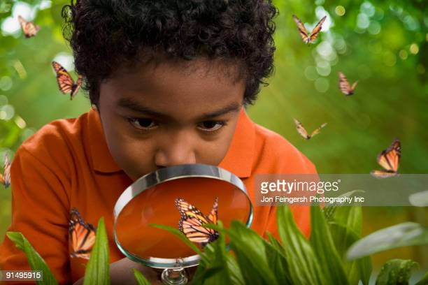 African boy looking at butterflies with magnifying glass