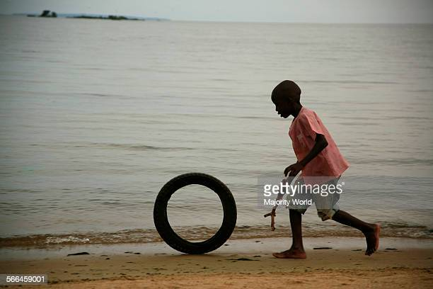 African boy plays with a rubber tyre and stick on the shores of Lake Victoria in Entebbe in Uganda