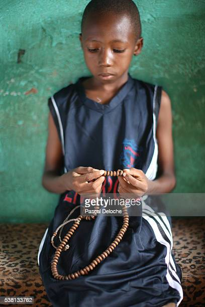 African boy praying at home.