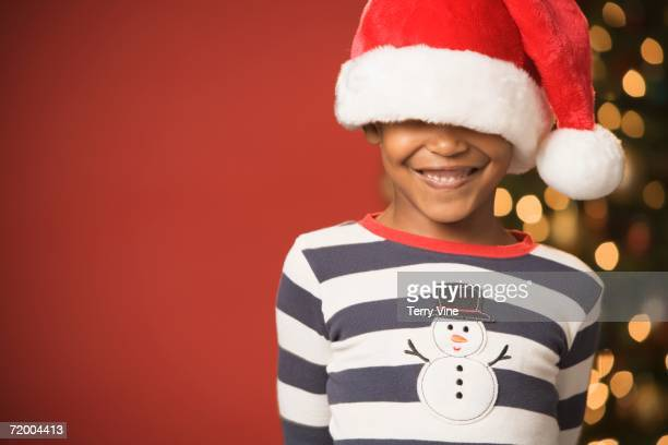 African boy smiling and wearing Santa Claus hat