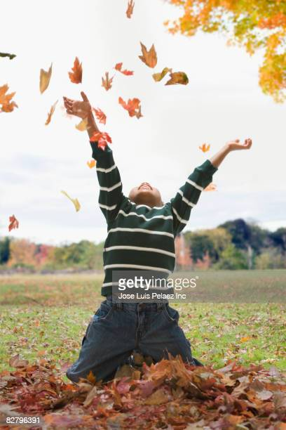 African boy throwing autumn leaves in air