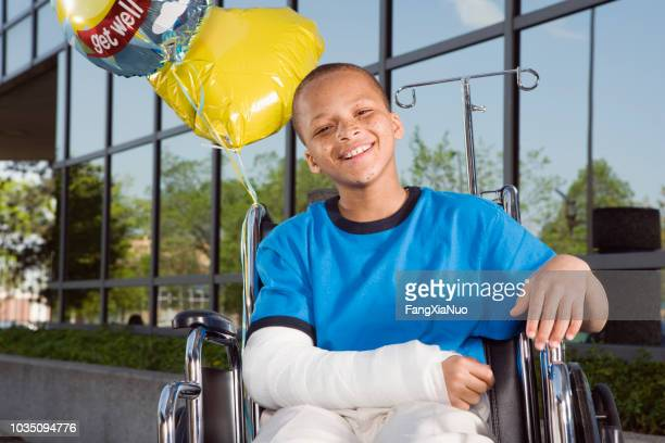 african boy with broken arm and balloons in wheelchair - broken arm stock pictures, royalty-free photos & images