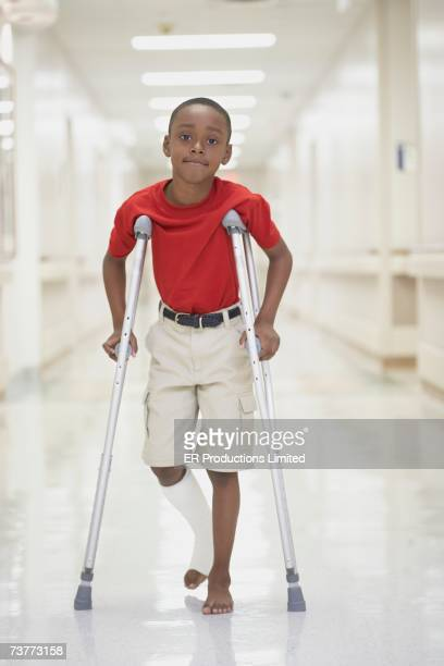 African boy with broken leg walking on crutches in hospital
