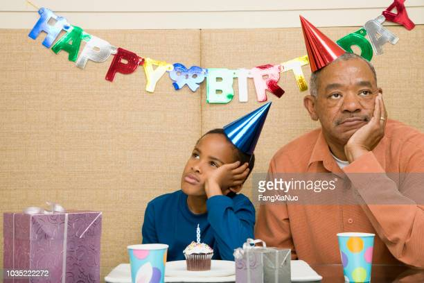 African boy with grandfather and cupcake at birthday party