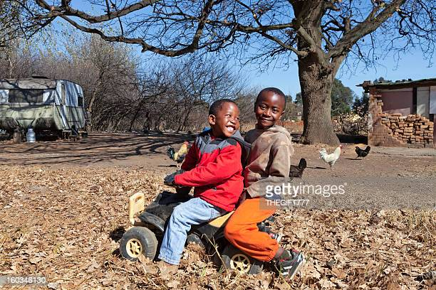 African boys playing with a push car