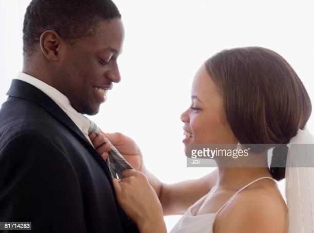 African bride adjusting groom's necktie