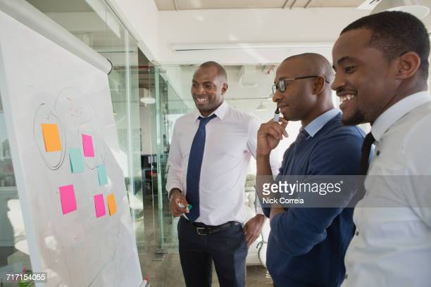 african business colleagues discussing at the office - nigerian men stock photos and pictures