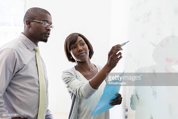 African business colleagues writing on the whiteboard