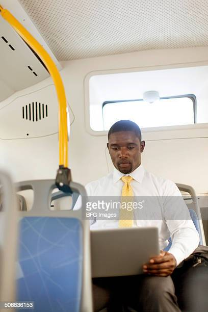 African business man sitting on bus using a laptop, Cape Town, South Africa