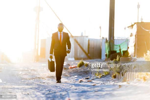 Hombre de negocios africanos caminando por vivienda rural