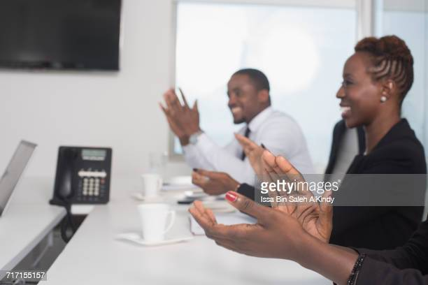 African business people clapping in conference room