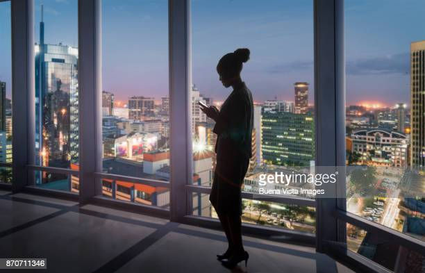 african business woman checking messages on smart phone - nairobi stock pictures, royalty-free photos & images