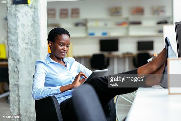 Africaine femme d'affaires à l'aide d'ordinateur tablette dans son bureau.