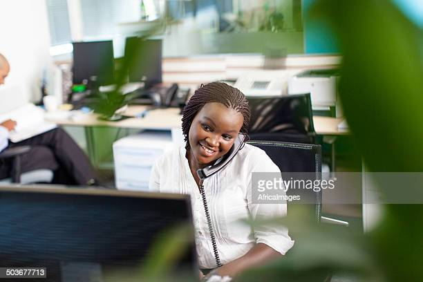 African business women smiling, having a telephone conversation