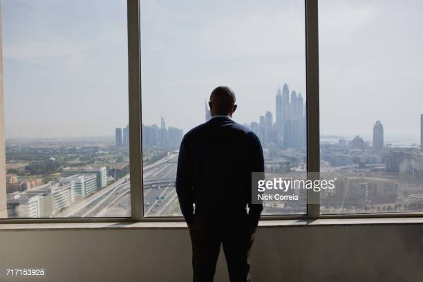 african businessman admiring city through window - nigerian men stock photos and pictures