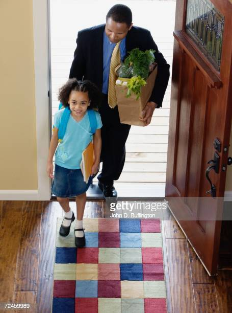 African businessman and daughter with groceries arriving at home