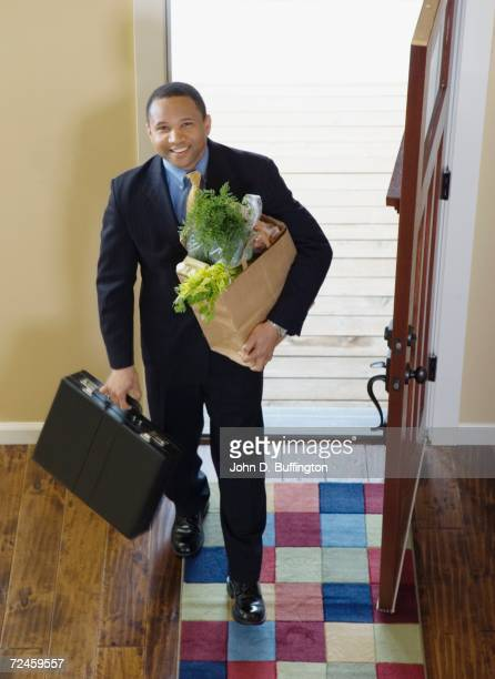 African businessman arriving at home with groceries