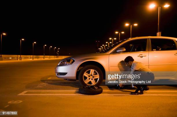 african businessman changing flat tire in parking lot - flat tire stock pictures, royalty-free photos & images