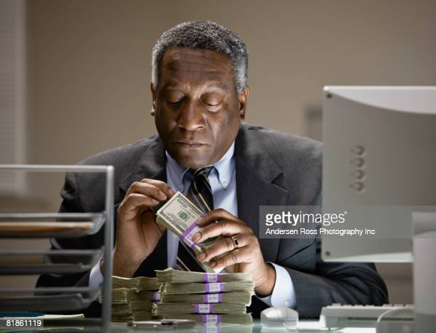 african businessman counting money - greed stock pictures, royalty-free photos & images