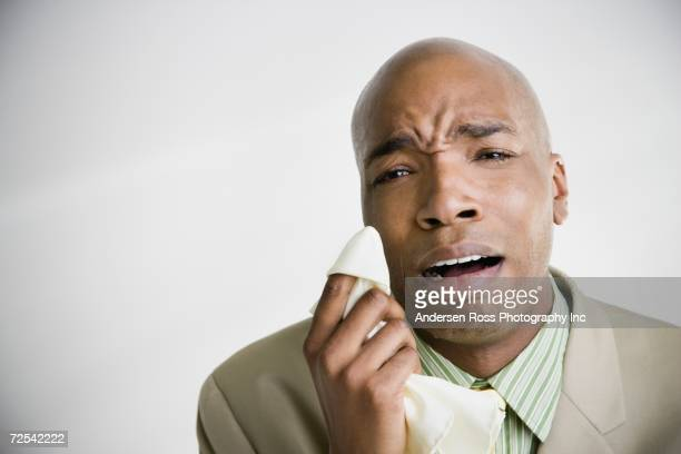 African businessman crying with tissue