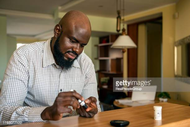 african businessman doing blood sugar test at home - insulin stock pictures, royalty-free photos & images