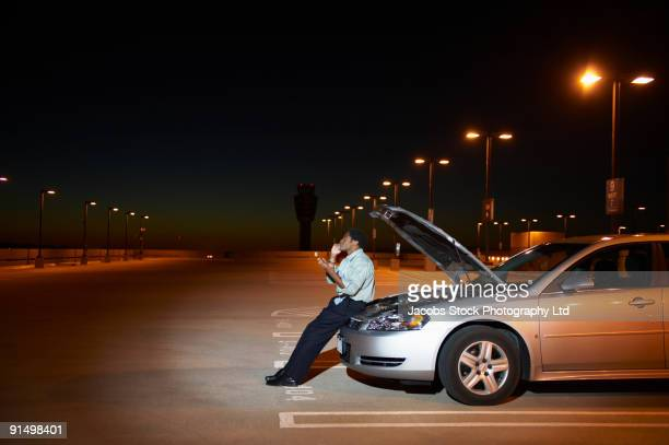 African businessman having car trouble in parking lot
