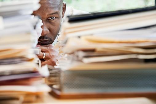African businessman hiding behind stack of paperwork - gettyimageskorea